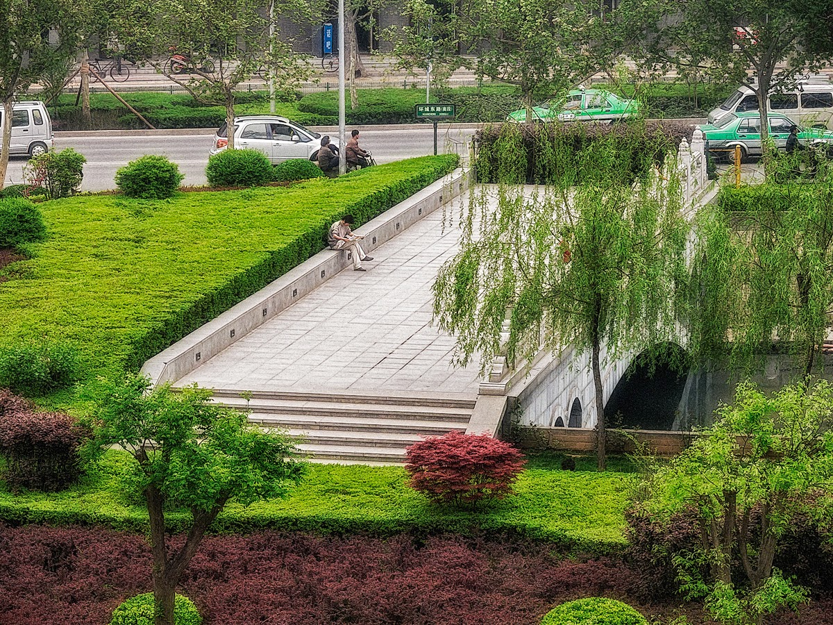 Photo: A Moat By Any Other Name is a park where one may rest and read a while.  Looking down to the outside of the old city wall in Xian, one sees the moat, now crisscrossed with bridges and lined with decorative trees, shrubs and flowers. It looks like a pleasant place to take a break from the busy traffic of this very big city.  #China   #Xian   #Travel