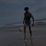 Man kicking a soccer ball on the beach near the ocean