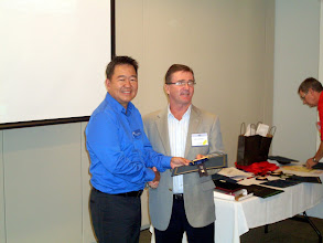 Photo: Darryl Somers (RVC RP) awarded the Silver Treasury Ribbon, Certificate - Goal, & Full Circle Chevron to Michael Wadham of Toronto Chapter, here received by Toronto's Michael Khaw (RVC MP)