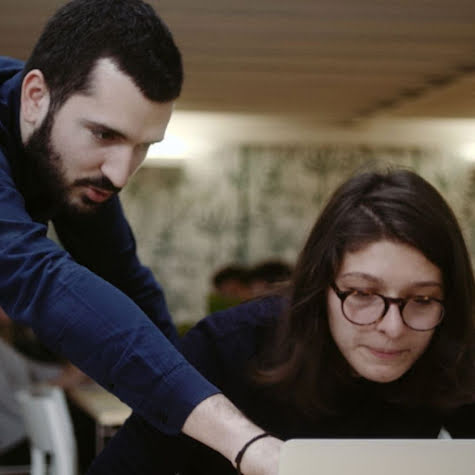 Un homme debout montre quelque chose sur l'écran à une femme assise devant un ordinateur.