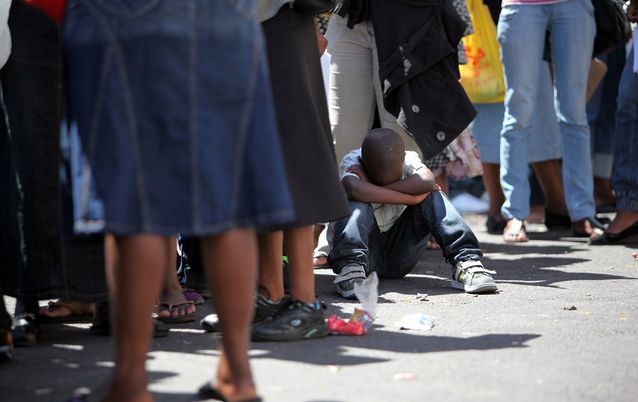 A migrant child waits in line at a Department of Home Affairs office.  Picture: SUNDAY TIMES