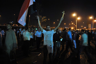 Photo: A man with an Egyptian flag in one hand and a cross in the other...