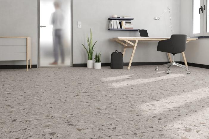 tendências de revestimentos e decoração para 2021 - escritório com piso de granilite em tom neutro, mesa de madeira com computador e cadeira preta, prateleiras  e vaso de planta no chão decorativo.