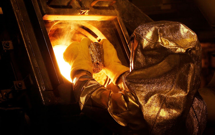Senior refinery technician Vincente Sandoval puts a gold 'button' into a furnace to be further refined to form gold doré bars at Newmont Mining's Carlin gold mine operation near Elko, Nevada, the US. Picture: REUTERS/RICK WILKING
