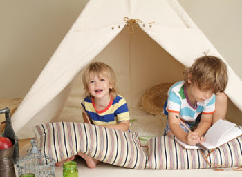 Two boys playing in front of teepee tent