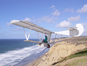 Photo: Bug2 is seen here launching from the cliff at Torrey Pines Gliderport, San Diego, California, in December, 2003. Floyd Fronius is the pilot, warmly dressed and holding a cup of coffee in his left hand. A smooth wind is blowing at about 30 mph. into the 300 foot high cliff.  Hang gliders can be seen high above, farther down the ridge.