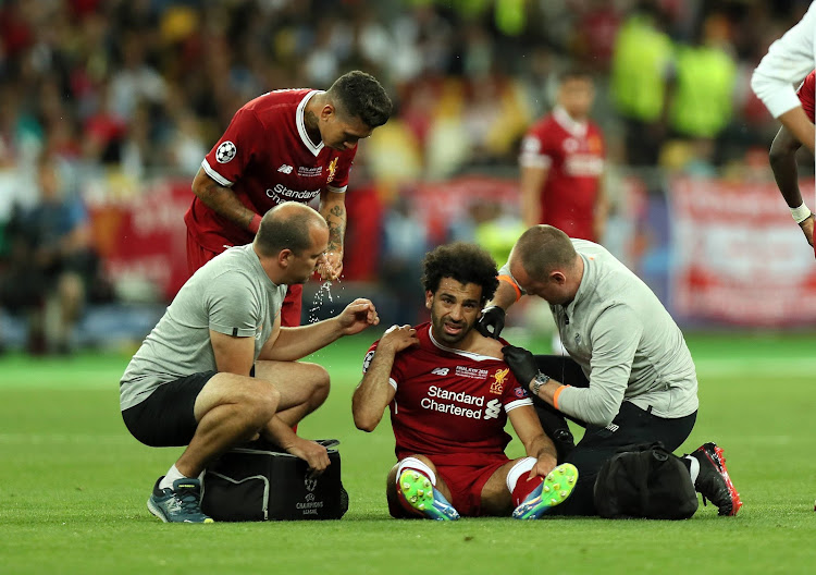 Mohamed Salah of Liverpool receives treatment for a shoulder injury during the UEFA Champions League final between Real Madrid and Liverpool on May 26, 2018 in Kiev, Ukraine.