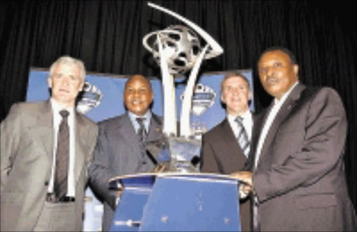 COMBATANTS: Officials of the clubs will take part in the Vodacom Challenge pose with trophy during the launch yesterday, from left, Manchester City coach Mark Hughes, Kaizer Chiefs boss Kaizer Motaung, City's executive chairman Garry Cook and Orlando Pirates chairman Irvin Khoza. 04/05/09. Pic. Veli Nhlapo. © Sowetan.