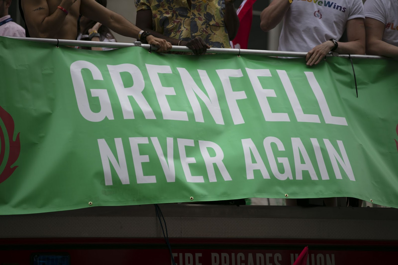 People holding a banner that says Grenfell never again