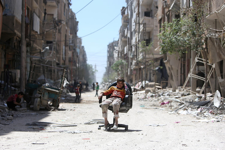 A boy sits on a chair along a damaged street at the city of Douma in Damascus, Syria April 16, 2018.
