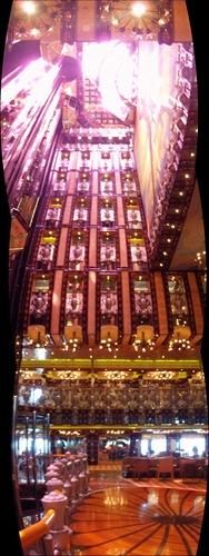 O Lobby do Legend. Três fotos panorâmicas em frente aos seus três elevadores panorâmicos, como quem olha para o tecto e vê a luz do sol no topo.