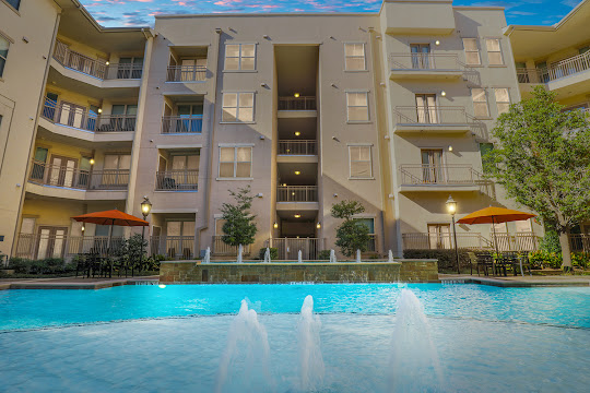 Mustang Station Apartment building and pool with fountains at dusk