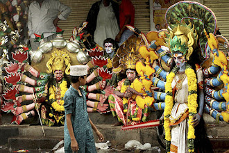 Photo: Indian artists rest in front of closed shops as it rains during a procession of 'Bonalu' festival in Hyderabad. (AP)