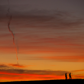 Holmes Lake Dam Sunset Couple by Gayle Mittan - Landscapes Sunsets & Sunrises ( couple, oranges, color, nebraska, clouds, hike, twisting cloud, summer, hill, walking, sunset, silhouette, vertical cloud, holmes lake,  )