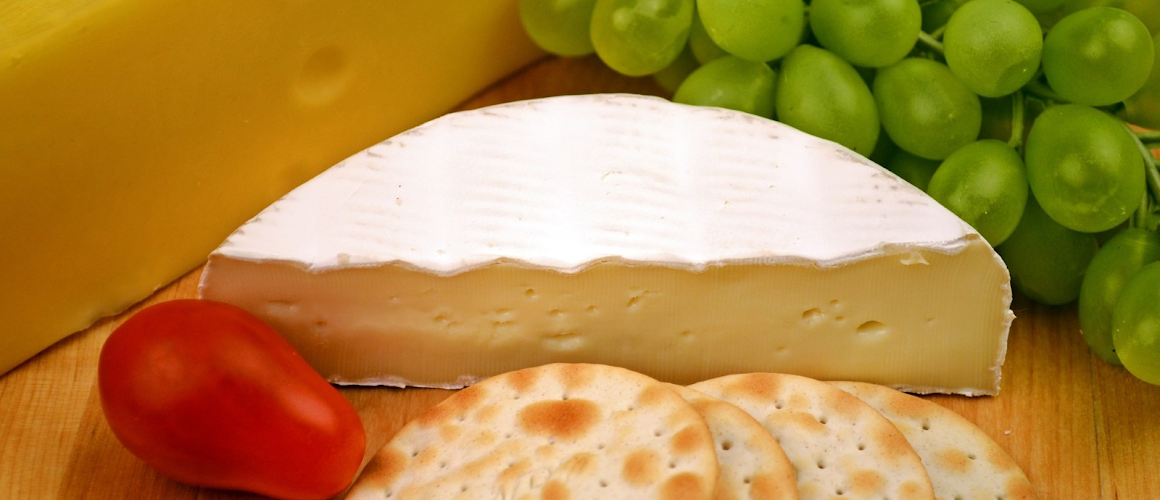a slice of brie cheese next to crackers and grapes