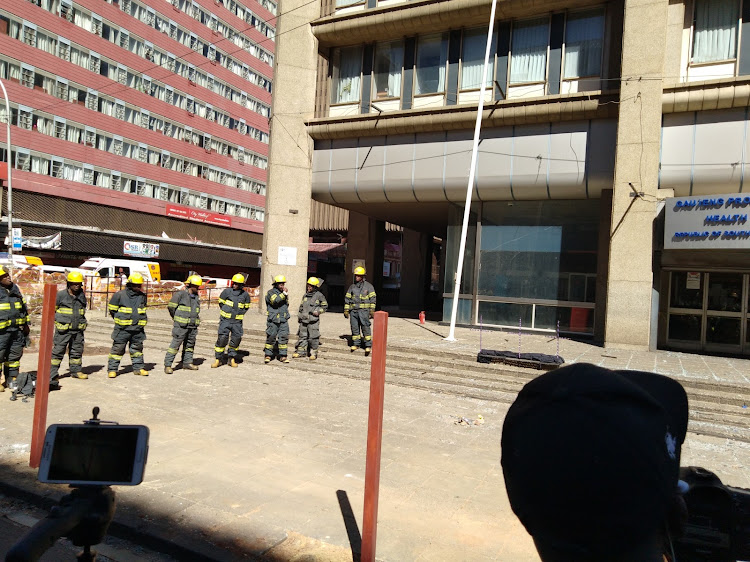 Firefighters wait for the wreath-laying ceremony to begin at the Bank of Lisbon building in Johannesburg on September 12 2018.