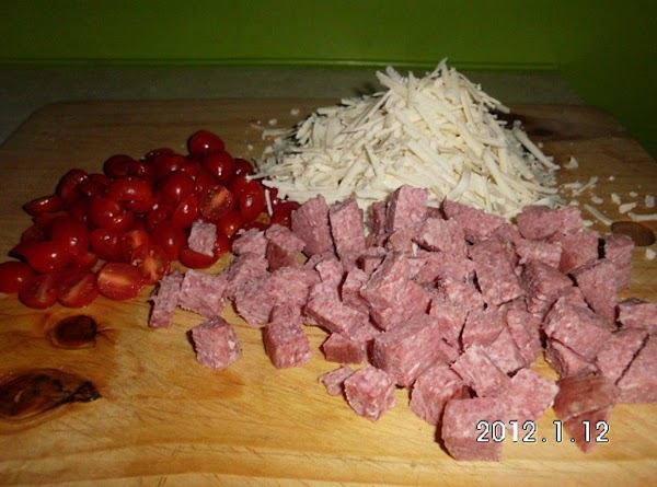 Half grape tomatoes, grate the Asiago, and cube the salami.