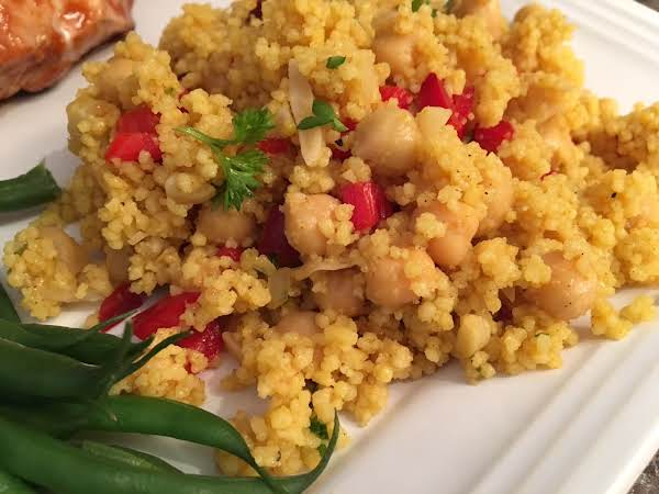 A Couscous Salad Served On A White Plate Next To Green Beans.