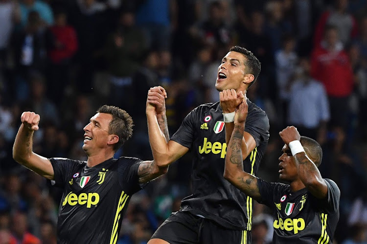 Juventus' Croatian forward Mario Mandzukic, Juventus' Portuguese forward Cristiano Ronaldo and Juventus' Brazilian forward Douglas Costa celebrate their team's victory at the end of the Italian Serie A football match Parma vs Juventus on September 1, 2018 at Ennio Tardini stadium in Parma.