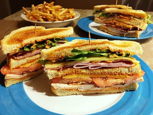 A Club Sandwich Served On A Blue Plate With A Bowl Of French Fries In The Background
