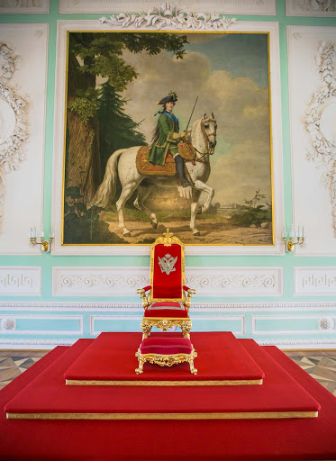 "Peterhof-Palace-Throne-Room.jpg - The east wall of Peterhof Palace's Throne Room displays the chair of state placed on a dais beneath the portrait ""Catherine II on Her Horse Brilliant."""