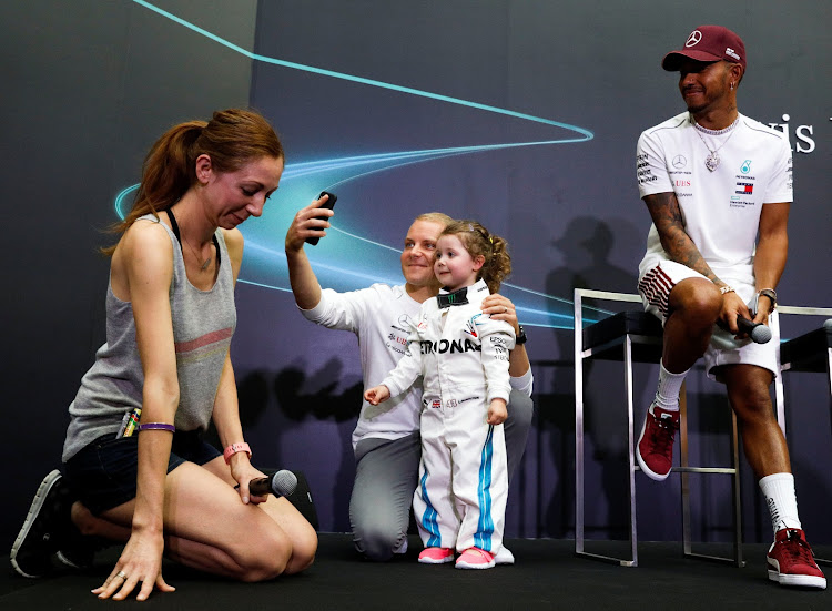 Mercedes' Lewis Hamilton and Valtteri Bottas interact with three-year-old Leila McKay during a publicity event in Singapore September 13, 2018.