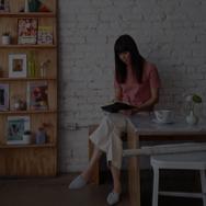 Woman sitting in breakfast nook, writing in journal