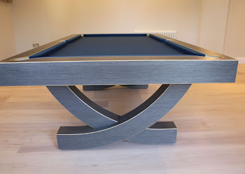 the arc pool table on wood flooring taken from the end view
