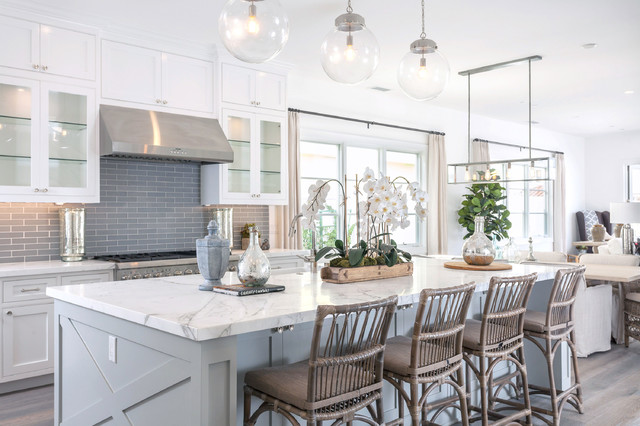 coastal white and grey kitchen with light grey center island. grey subway tile backsplash is surrounded by bright white shaker kitchen cabinets