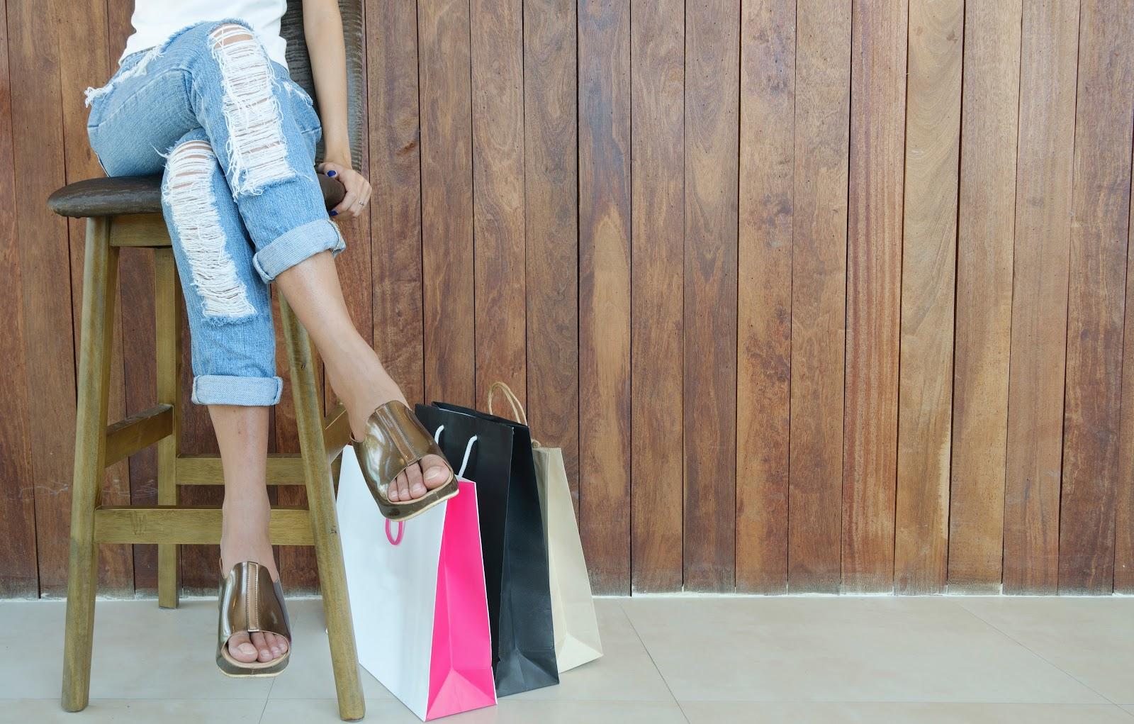 רגלי אישה בג'ינס עם שקיות קניות על הריצפה