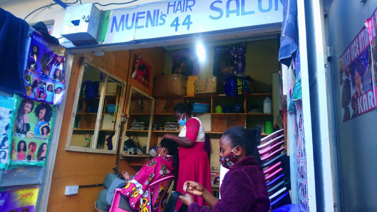Hairdressers at Kenyatta Market wearing masks while working on a client.