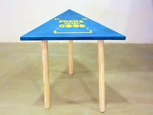 table scandinave en béton ciré forme triangle avec incrustation de logo