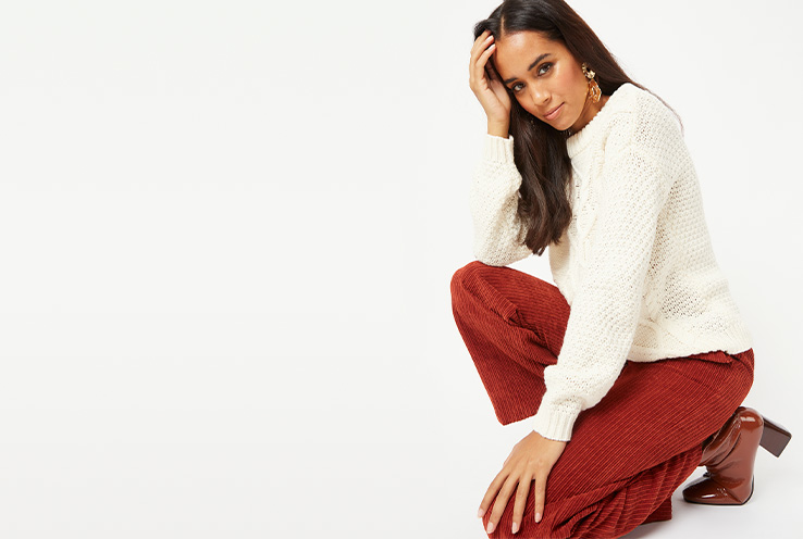 Woman wearing a cream jumper with red corduroy trousers and boot heels