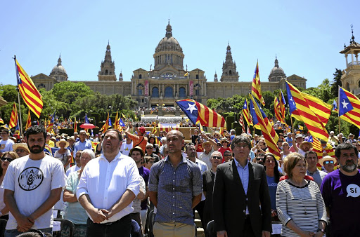 Manchester City's manager Pep Guardiola (centre) and Catalan regional president Carles Puigdemont (on the right of Guardiola) take part in a pro-independence rally in Barcelona, Spain, on June 11 2017. Picture: REUTERS/ALBERT GEA