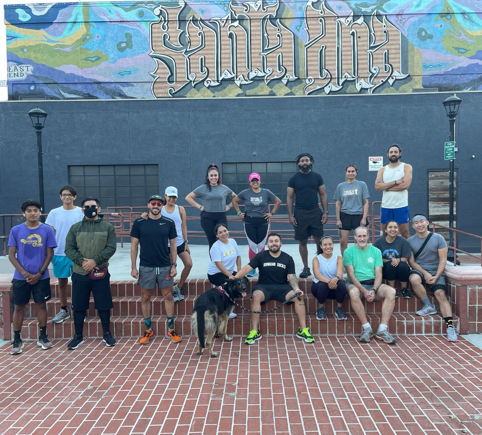A group of runners pose after a 3-mile run in front of a mural that reads, Santa Ana. There is a dog in the front row, he looks like a German Shepherd.