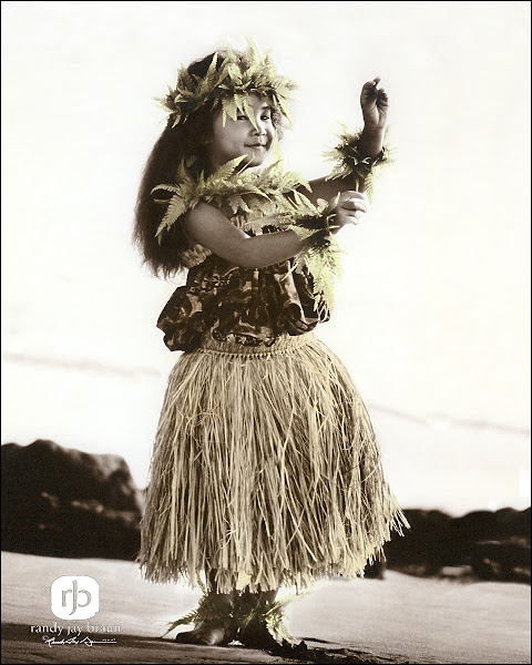 Photo: Nohea - Charming This little hula dancerʻs smile is contagious. Four-year-old Jessica Lei wears a raffia palm skirt and adornments made from Palapalai ferns - one of the native plants considered precious to Laka, goddess of the Hawaiian hula. © www.RandyJayBraun.com