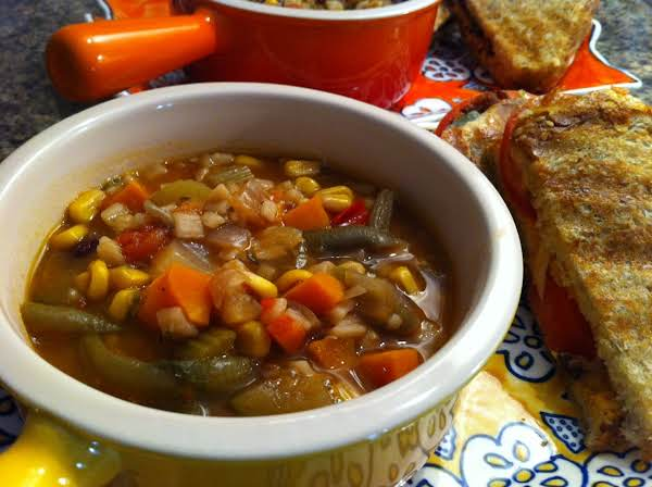 Vegetable Soup In Two Bowls With Sandwiches Next To Them.