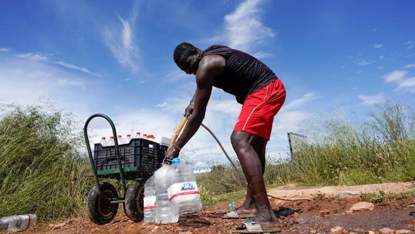 Un inmigrante haciendo acopio de agua en el campo.