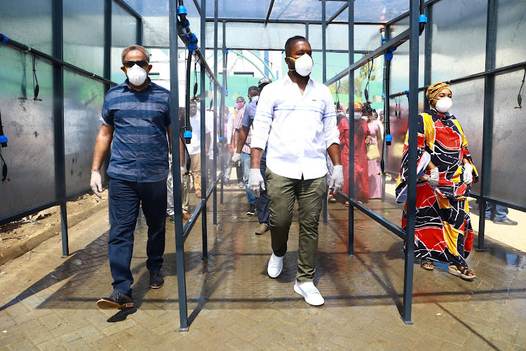 Businessman Suleiman Shahbal, Mombasa Governor Hassan Joho and Likoni MP Mishi Mboko pass through the sanitising spray booth at the Likoni crossing channel