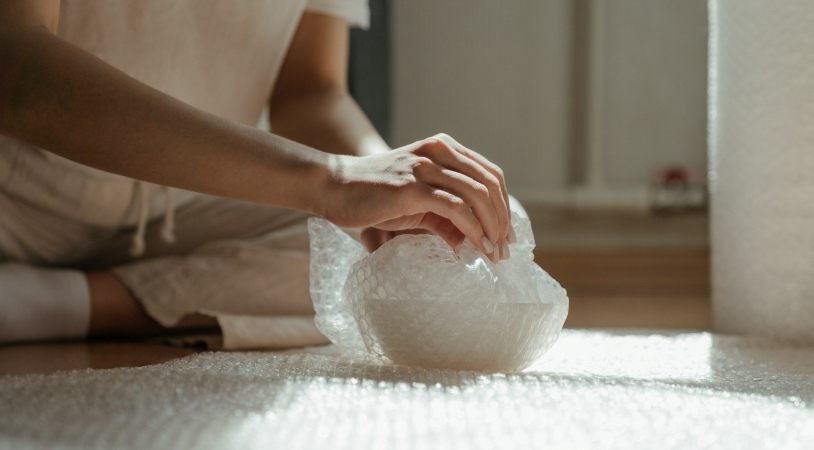 woman wrapping a dish in bubble wrap