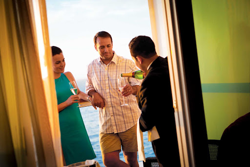 ncl-butler-champagne.jpg - A butler serves Champagne to a couple in their suite on a Norwegian Cruise Line sailing.