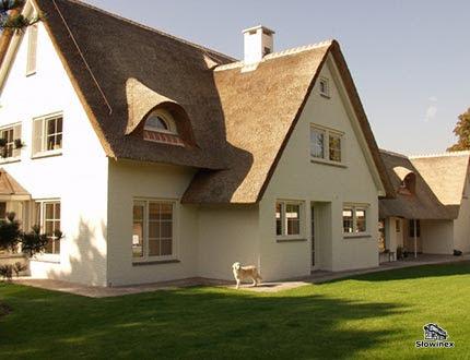 Elegancki dwupoziomowy domek o białej fasadzie i trzcinowym dachu