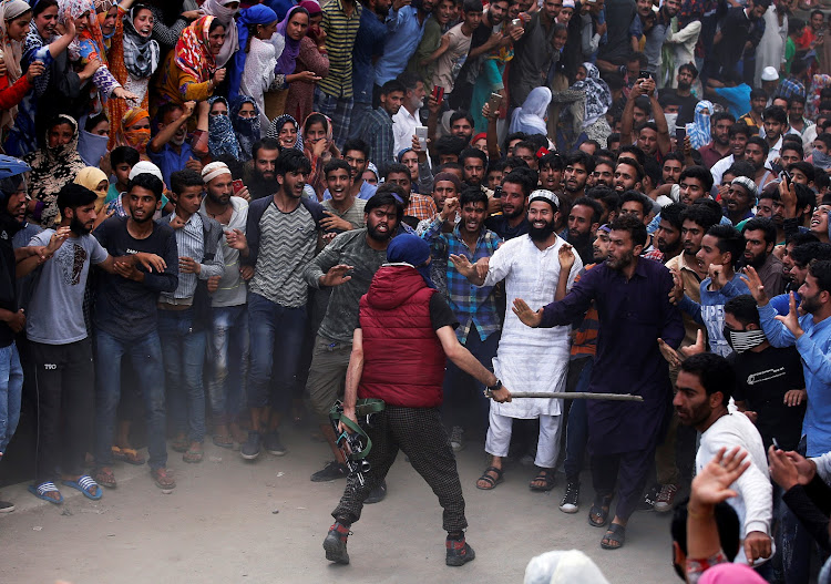 A suspected militant keeps people away before offering a gun salute during the funeral of Bilal Ahmed, who according to local media was killed in a gun battle with Indian security forces in Khudwani.