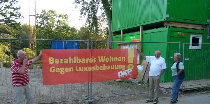 Protestierende am Bauzaun, Transparent: «Bezahlbares Wohnen gegen Luxusbebauung! DKP».
