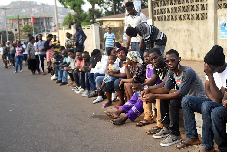 People wait to cast their vote during Sierra Leone's presidential election in Freetown.