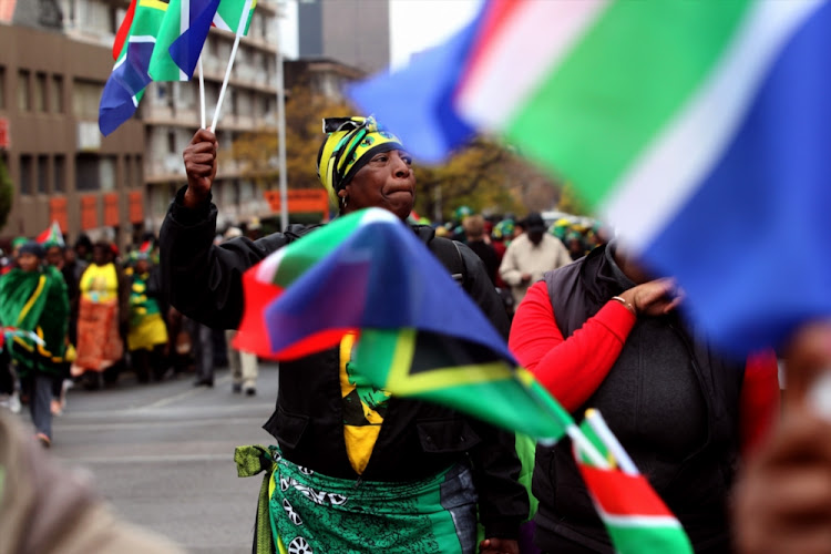 People carrying South African flags gather during the Women's Day march to the Union Buildings on August 9 2018 in Pretoria.