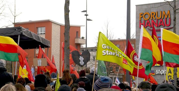 Demonstranten mit Fahnen. Rechts: «Forum Hanau».