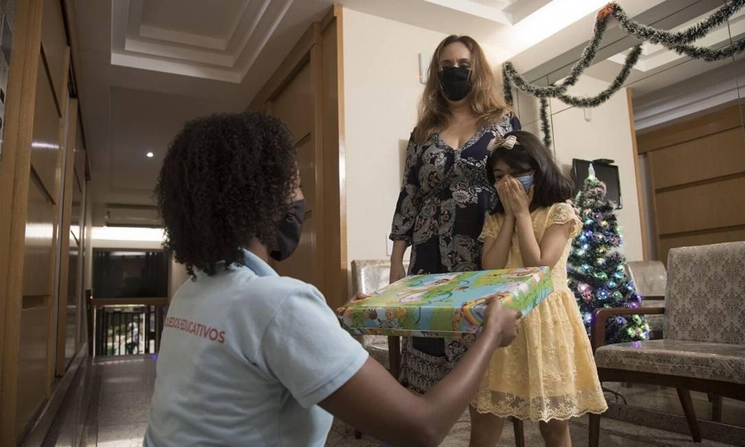 A pequena Elisa, de 7 anos, recebe seu presente das mãos da entregadora Victoria Foto: Ana Branco / Agência O Globo