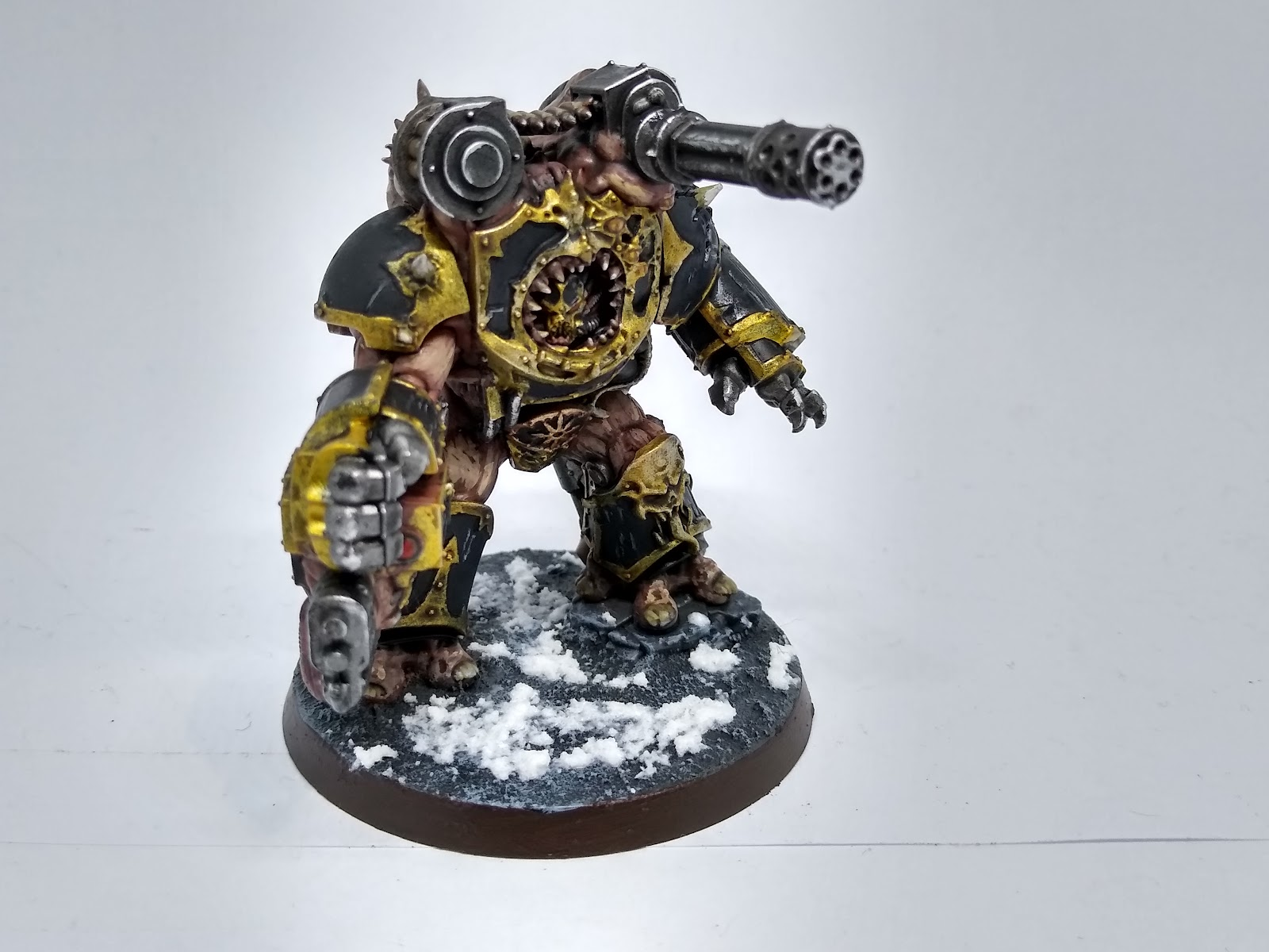 A model Obliterator, a massive warrior with multiple large guns, painted in black and gold with pale flesh.