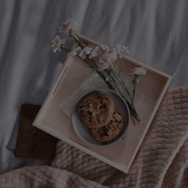 Cookies and flowers on a pink tray on a bed